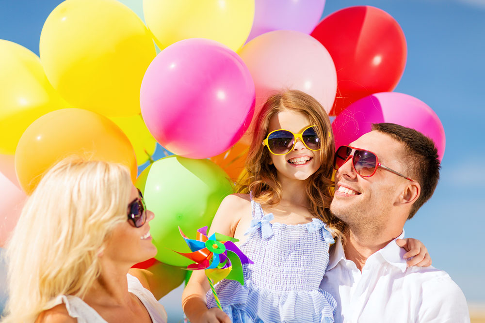 Parents & Daughter in front of Colorful Balloons